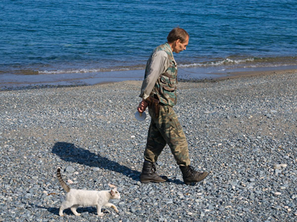 man-walks-cat-beach